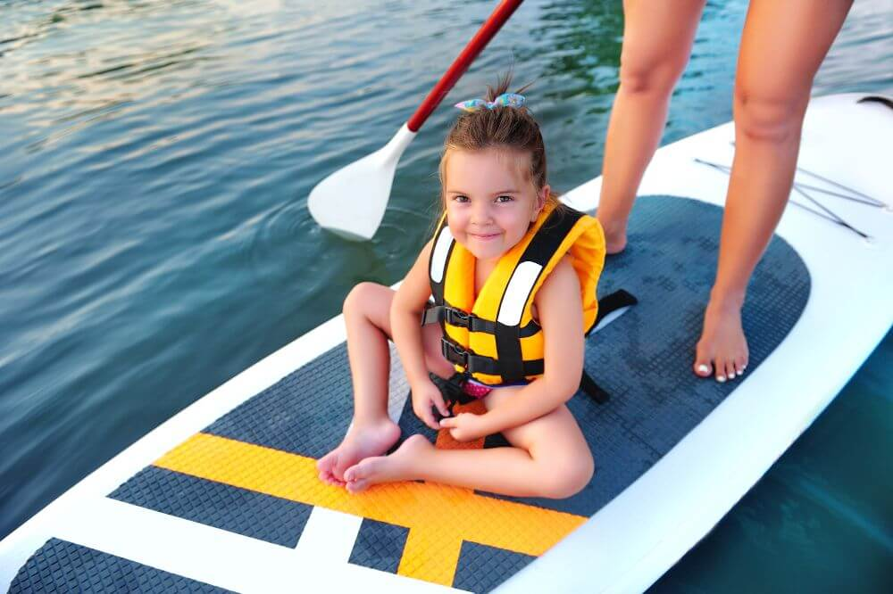 Little girl with life vest enjoying SUP ride
